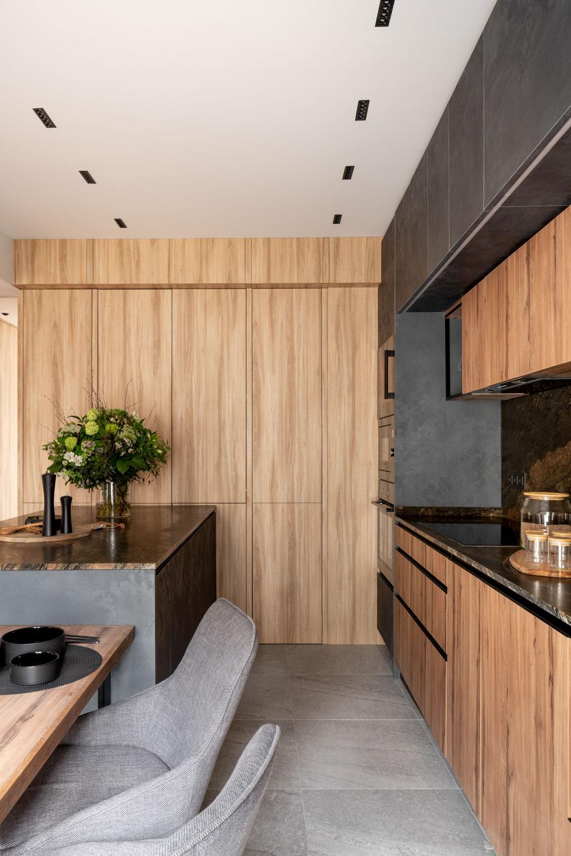 Imagen de cocina, mobiliario de color negro y maderas, uso de mármoles oscuros